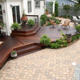 This is an example of a large traditional back patio in DC Metro with decking and an awning.