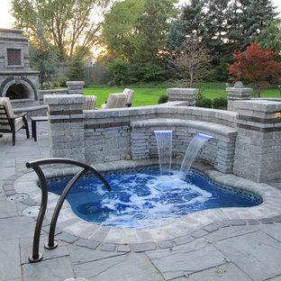 Immagine di un grande patio o portico rustico dietro casa con un focolare, pavimentazioni in pietra naturale e nessuna copertura