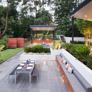 Idee per un grande patio o portico minimal dietro casa con pedane e un gazebo o capanno