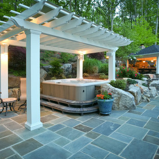 Photo of a large traditional backyard patio in DC Metro with an outdoor kitchen, natural stone pavers and a gazebo/cabana.