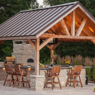 Idées déco pour une grande terrasse arrière classique avec des pavés en pierre naturelle et un gazebo ou pavillon.