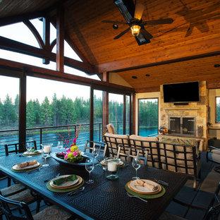 Ispirazione per un patio o portico stile rurale di medie dimensioni e dietro casa con pavimentazioni in cemento e un tetto a sbalzo