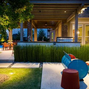 Esempio di un grande patio o portico boho chic dietro casa con pavimentazioni in cemento e una pergola