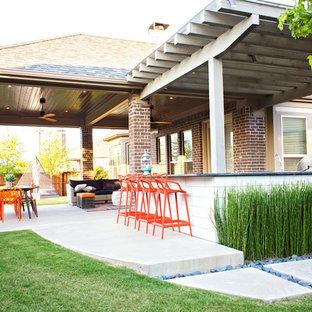 Idee per un grande patio o portico bohémian dietro casa con pavimentazioni in cemento e una pergola