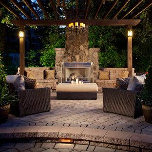 Immagine di un grande patio o portico american style dietro casa con un focolare, pavimentazioni in mattoni e una pergola
