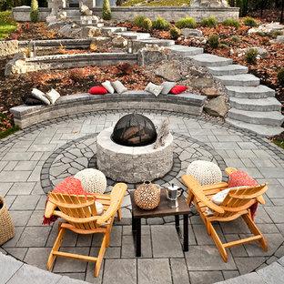 Ejemplo de patio clásico, grande, sin cubierta, en patio trasero, con brasero y adoquines de piedra natural
