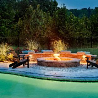 Idee per un ampio patio o portico classico dietro casa con un focolare e lastre di cemento