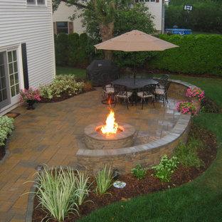 Foto di un patio o portico classico di medie dimensioni e dietro casa con nessuna copertura, un focolare e piastrelle