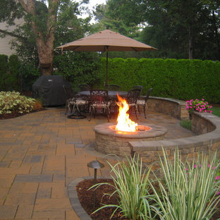 Inspiration for a mid-sized timeless backyard stone patio kitchen remodel in New York with no cover