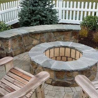 Esempio di un patio o portico stile americano di medie dimensioni e dietro casa con un focolare, pavimentazioni in pietra naturale e nessuna copertura