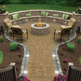 Inspiration for a large timeless backyard stone patio remodel in Providence with a fire pit and no cover