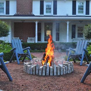 Ispirazione per un patio o portico country di medie dimensioni e in cortile con un focolare, ghiaia e una pergola