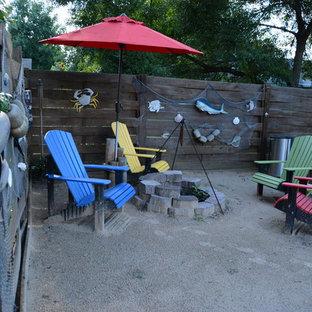 Foto di un patio o portico tropicale di medie dimensioni e dietro casa con un focolare, ghiaia e nessuna copertura