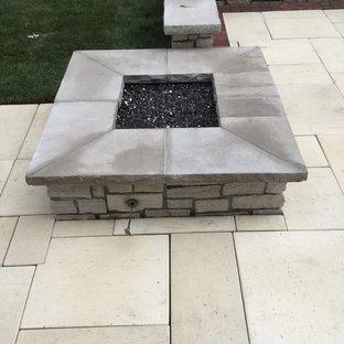 Esempio di un patio o portico tradizionale di medie dimensioni e dietro casa con un focolare, piastrelle e nessuna copertura