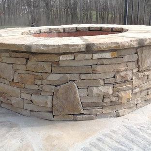 Ispirazione per un patio o portico american style di medie dimensioni e dietro casa con un focolare e pavimentazioni in pietra naturale