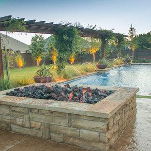 Esempio di un patio o portico stile americano di medie dimensioni e dietro casa con un focolare, lastre di cemento e una pergola