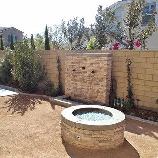 Idee per un patio o portico mediterraneo dietro casa con un focolare e graniglia di granito