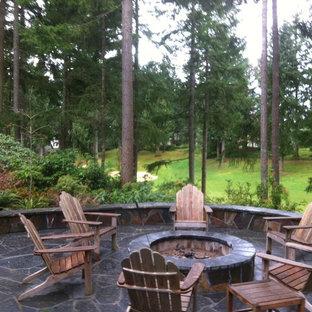 Foto di un patio o portico american style dietro casa e di medie dimensioni con un focolare, pavimentazioni in pietra naturale e nessuna copertura