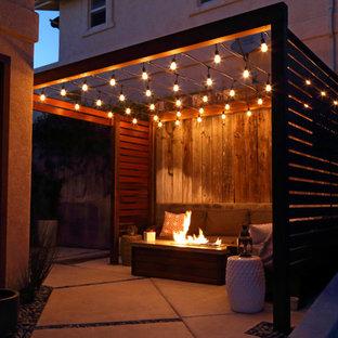 Esempio di un piccolo patio o portico moderno in cortile con un focolare, lastre di cemento e una pergola