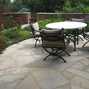 Immagine di un patio o portico boho chic di medie dimensioni e in cortile con un giardino in vaso, pavimentazioni in pietra naturale e nessuna copertura