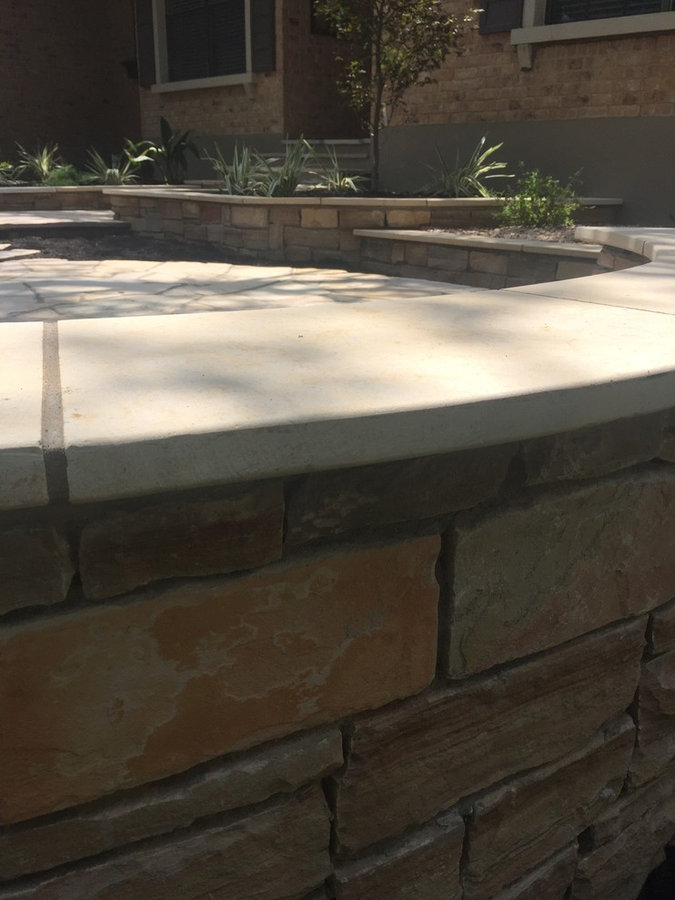 Flagstone patio w/ random pattern stone walls and raised beds