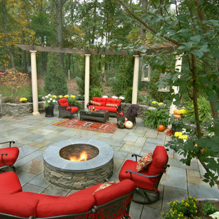 Example of a mid-sized classic backyard stone patio design in DC Metro with a fire pit and a pergola