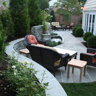 Photo of a mid-sized contemporary backyard patio in DC Metro with natural stone pavers, a water feature and no cover.