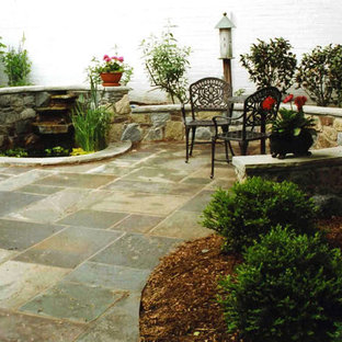 Immagine di un patio o portico boho chic dietro casa e di medie dimensioni con fontane, pavimentazioni in pietra naturale e nessuna copertura