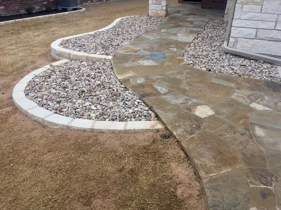 Flagstone sidewalk and entryway w/ new river rock beds using limestone borders