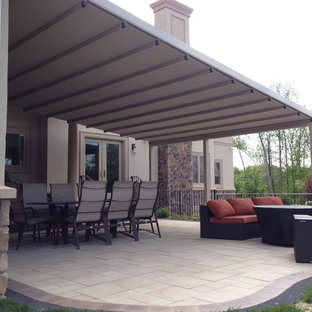 This is an example of a medium sized classic back patio in New York with decking and an awning.