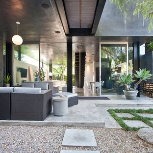 Design ideas for a mid-sized contemporary courtyard patio in Los Angeles with a fire feature, concrete slab and a roof extension.
