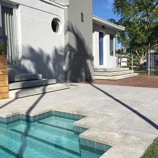 Ispirazione per un grande patio o portico minimalista dietro casa con piastrelle