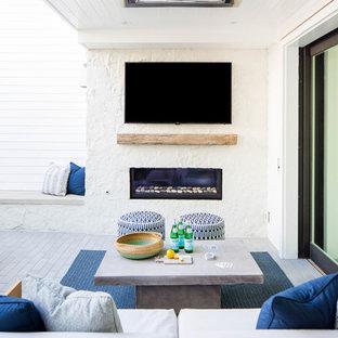 Esempio di un patio o portico country di medie dimensioni e in cortile con un caminetto, pavimentazioni in cemento e un tetto a sbalzo
