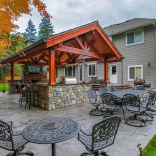 Immagine di un grande patio o portico american style dietro casa con lastre di cemento e un tetto a sbalzo
