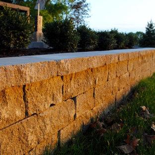 Esempio di un grande patio o portico minimal con un focolare, pavimentazioni in cemento e una pergola