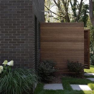Ispirazione per un patio o portico minimalista dietro casa con pavimentazioni in pietra naturale e un tetto a sbalzo