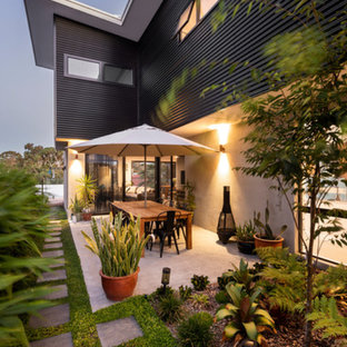 This is an example of a medium sized modern side patio in Perth with a living wall, concrete slabs and an awning.