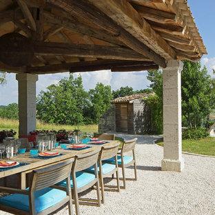 Idées déco pour une grande terrasse et balcon arrière avec du gravier et un gazebo ou pavillon.