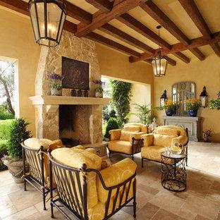 Idee per un patio o portico mediterraneo con piastrelle, un tetto a sbalzo e un caminetto