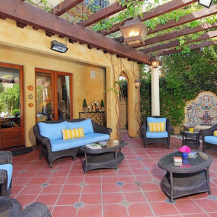 Example of a tuscan patio fountain design in Los Angeles with a pergola