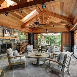Cette photo montre une grande terrasse arrière montagne avec un foyer extérieur, une extension de toiture et des pavés en pierre naturelle.