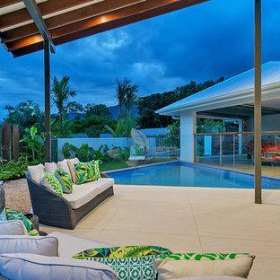 Idee per un grande patio o portico tropicale dietro casa con piastrelle e un gazebo o capanno
