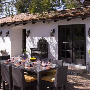На фото: дворик в средиземноморском стиле с покрытием из плитки без защиты от солнца с