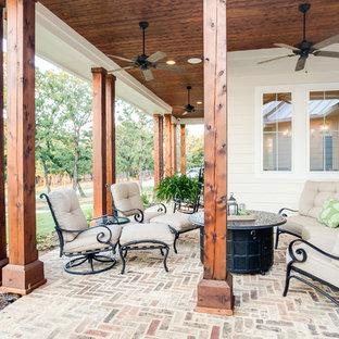 Idee per un grande patio o portico country davanti casa con un giardino in vaso, pavimentazioni in pietra naturale e un tetto a sbalzo