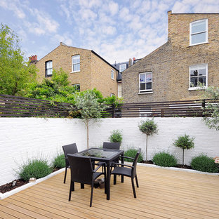 Contemporary patio in London with decking and no cover.