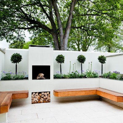 Example of a small trendy backyard stone patio design in Wiltshire with a fire pit
