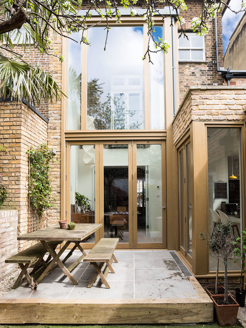 Photo Of A Contemporary Back Patio In London With Concrete Paving And No  Cover.