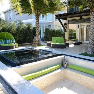 Cette image montre une très grande terrasse avec une cuisine extérieure arrière design avec une pergola et des pavés en pierre naturelle.