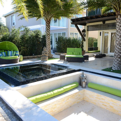 Example of a huge trendy backyard stone patio kitchen design in Miami with a pergola