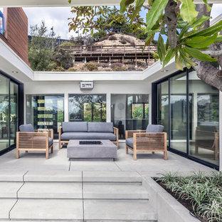 Diseño de patio actual, de tamaño medio, sin cubierta, en patio trasero, con brasero y losas de hormigón
